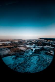 Bela foto de uma asa de avião pela janela sobre uma paisagem coberta de neve