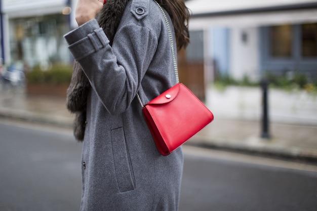 Bela foto de uma bolsa branca usando uma senhora com um casaco escuro em uma estrada