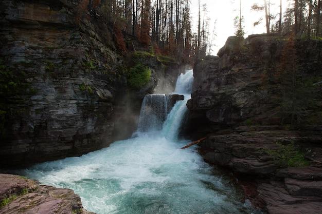Bela foto de uma cachoeira no meio de um penhasco, rodeado por árvores