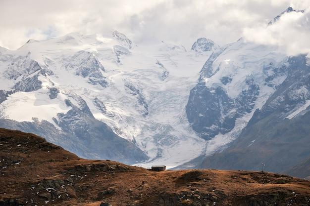 Bela foto de uma casa à beira do precipício com montanhas nevadas