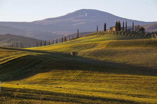 Bela foto de uma casa de campo no meio de um campo cercado por colinas sob o céu claro