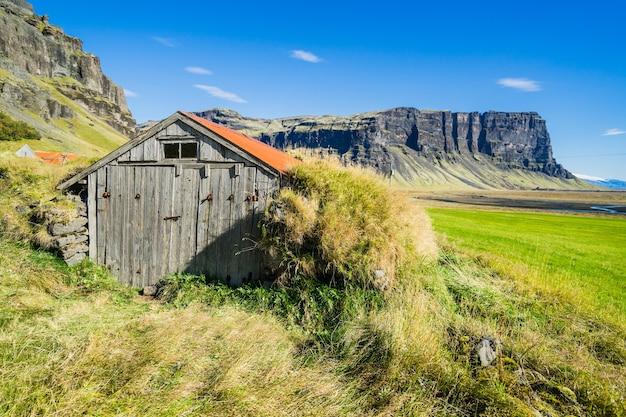 Bela foto de uma casa de madeira em um campo na islândia