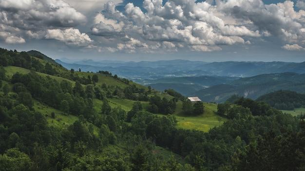 Bela foto de uma casa em uma paisagem montanhosa verde em um céu nublado