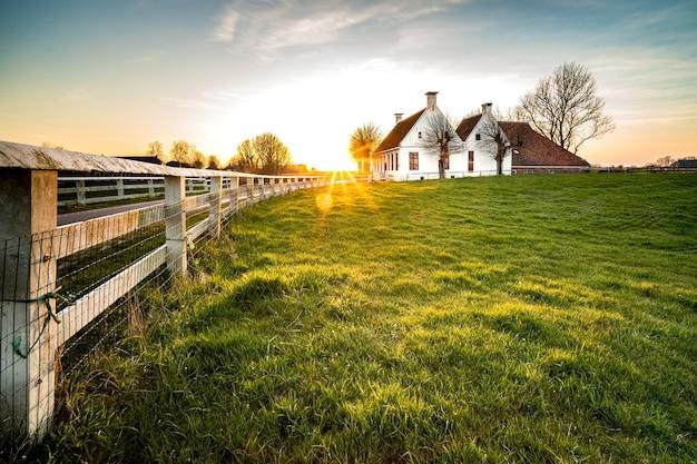 Bela foto de uma cerca que leva a uma casa em uma área de grama verde