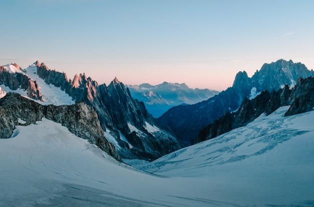 Bela foto de uma colina de neve rodeada por montanhas com o céu rosa claro