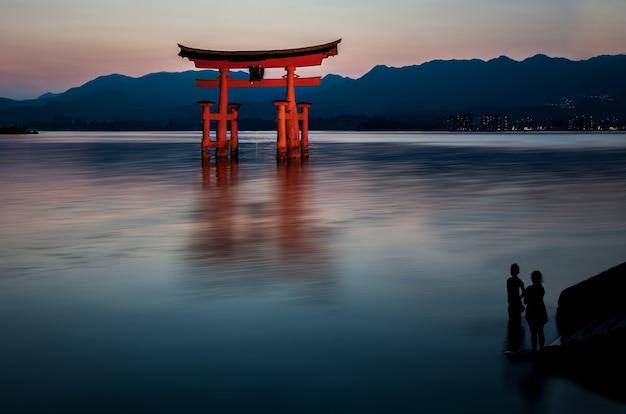 Bela foto de uma construção vermelha na água com silhuetas humanas olhando para ele