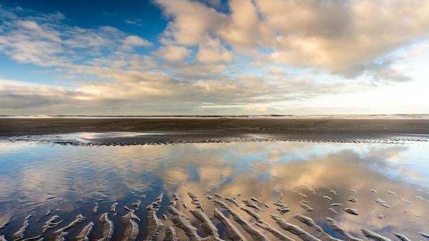 Bela foto de uma costa arenosa úmida com lago de água sob um céu azul nublado