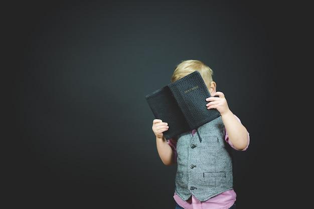 Bela foto de uma criança segurando uma bíblia aberta