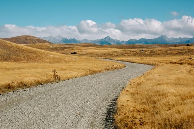 Bela foto de uma estrada em lindis pass lindamente iluminada pelo sol da tarde na nova zelândia