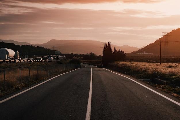 Bela foto de uma estrada vazia no campo durante o dia