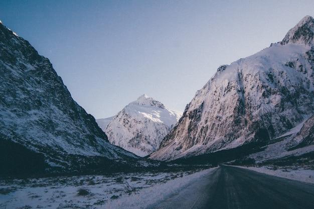 Bela foto de uma estrada vazia passando por altas montanhas rochosas cobertas de neve