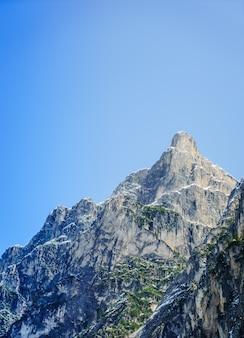 Bela foto de uma grande montanha rochosa com claro céu azul