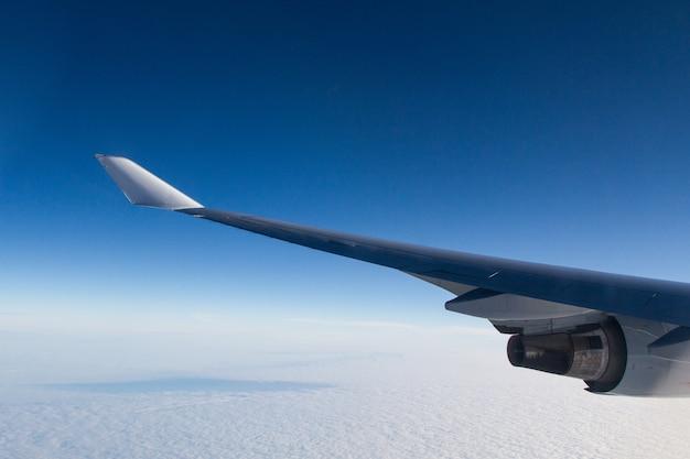 Bela foto de uma janela de avião das asas sobre as nuvens