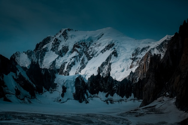 Bela foto de uma montanha de neve com um céu azul escuro