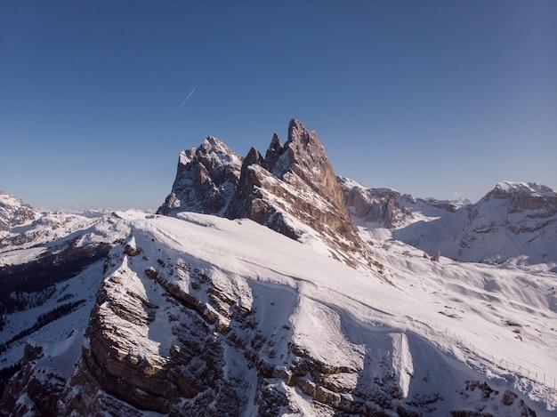 Bela foto de uma montanha íngreme coberta de neve branca durante o inverno