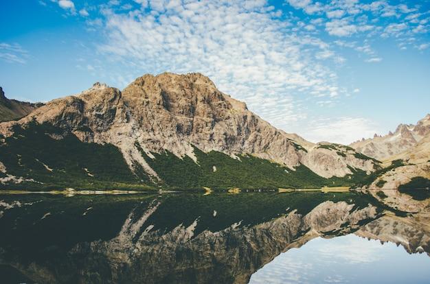 Bela foto de uma montanha rochosa ao lado de um lago com reflexo na água