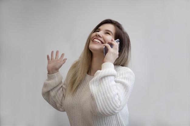 Bela foto de uma mulher animada ao ligar de seu telefone