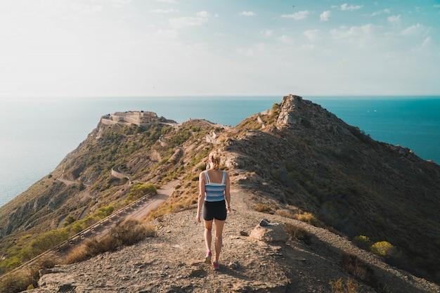 Bela foto de uma mulher caminhando em uma colina ao lado do oceano com o céu ensolarado ao fundo