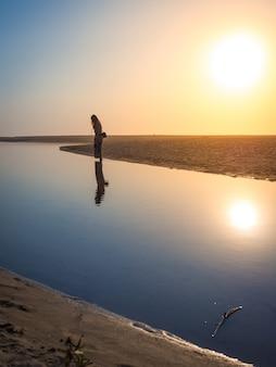 Bela foto de uma mulher caminhando na praia sob o sol