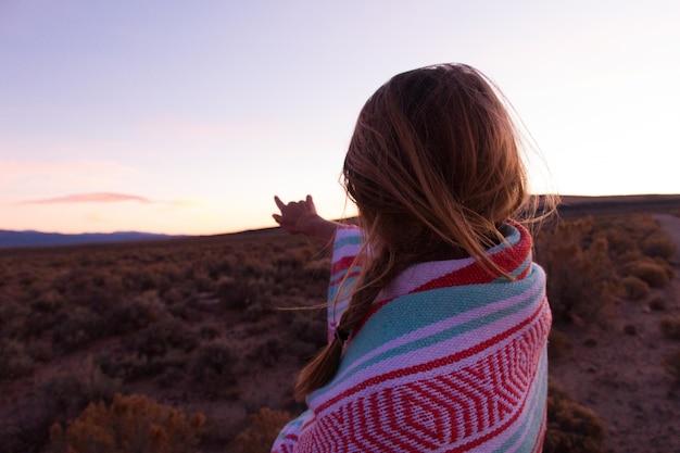 Bela foto de uma mulher coberta de cobertores, olhando para a distância