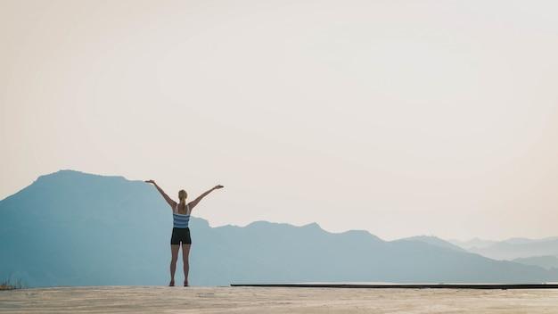 Bela foto de uma mulher em pé no chão com as silhuetas das colinas ao fundo