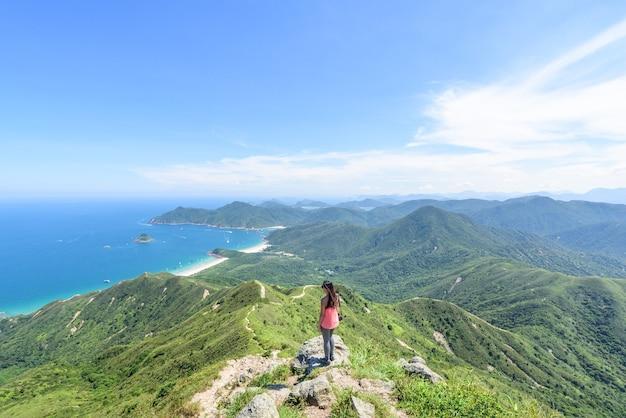 Bela foto de uma mulher em um penhasco com uma paisagem de colinas arborizadas e um oceano azul