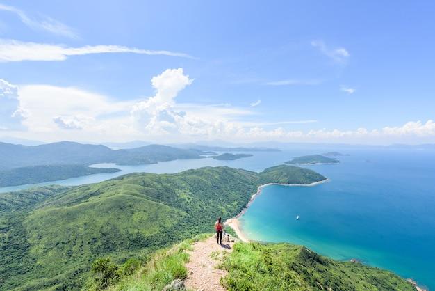 Bela foto de uma mulher em uma paisagem de colinas arborizadas e um oceano azul