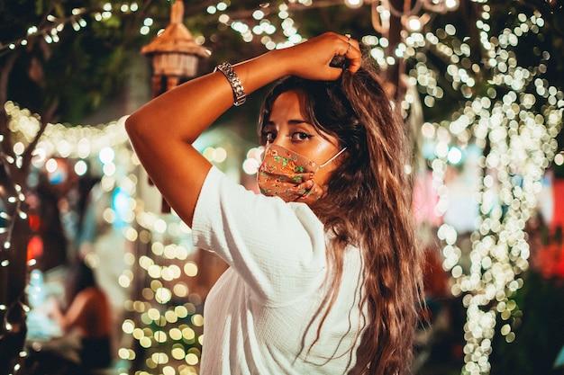 Bela foto de uma mulher europeia bronzeada usando uma máscara floral em um parque de diversões