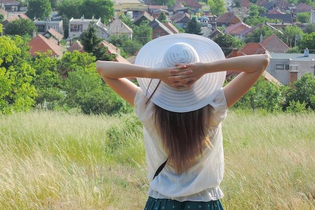 Bela foto de uma mulher segurando um chapéu branco, apreciando a vista e o ar fresco em um campo gramado