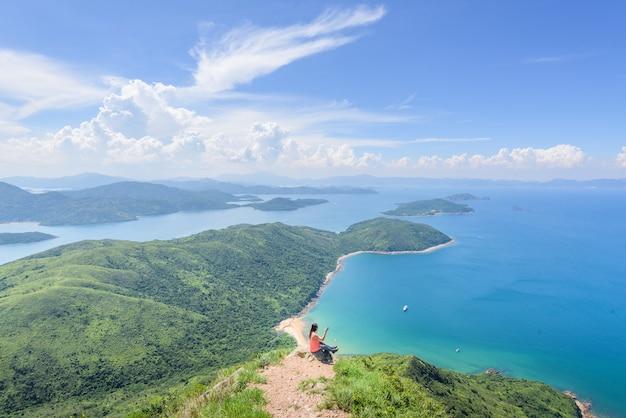 Bela foto de uma mulher sentada em um penhasco com uma paisagem de colinas arborizadas e um oceano azul