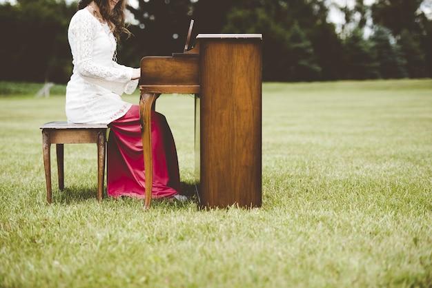 Bela foto de uma mulher tocando piano em um campo gramado com um fundo desfocado