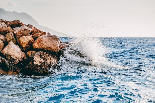Bela foto de uma onda forte do mar atingindo as rochas