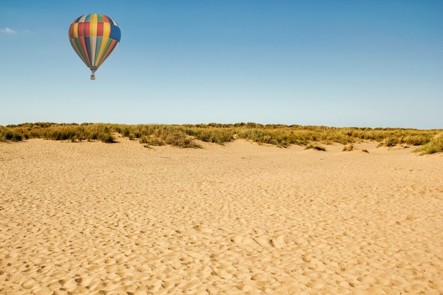 Bela foto de uma paisagem arenosa com um balão de ar quente voador