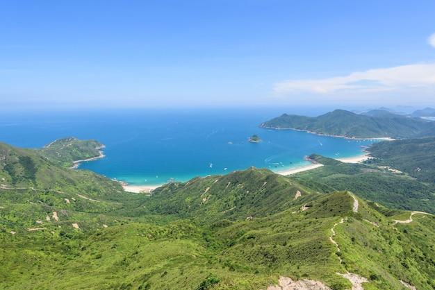 Bela foto de uma paisagem de colinas arborizadas e um oceano azul