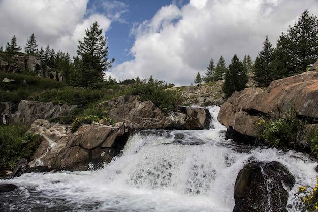 Bela foto de uma pequena cachoeira com formações rochosas e árvores ao redor em um dia nublado