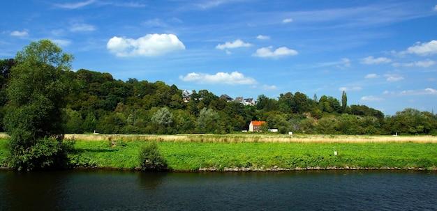 Bela foto de uma pequena casa ao redor de árvores verdes e um campo gramado em um dia nublado