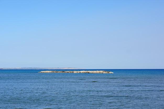 Bela foto de uma pequena ilha coberta de pedras no meio de um lago