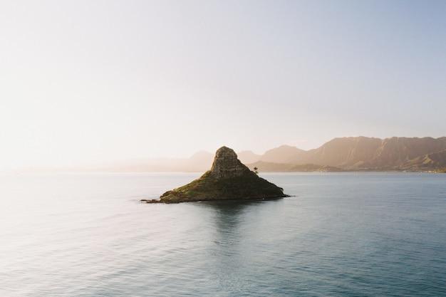 Bela foto de uma pequena ilha no centro do mar aberto com um cenário do nascer do sol