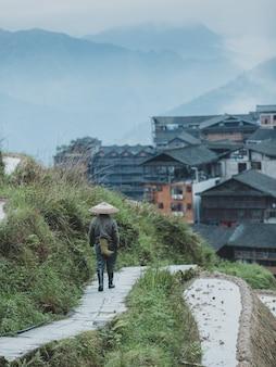 Bela foto de uma pessoa caminhando por um caminho em um terraço em uma cidade chinesa