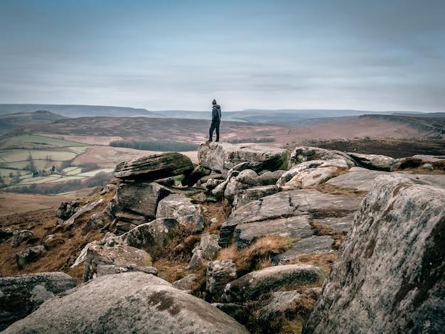 Bela foto de uma pessoa em pé sobre as rochas, olhando para o vale à distância