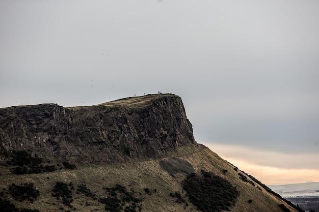 Bela foto de uma pessoa parada no topo de um penhasco à distância