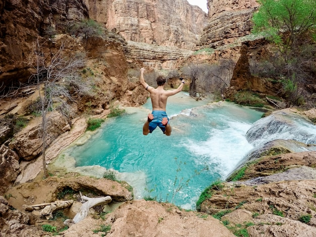 Bela foto de uma pessoa vestindo maiô pulando de um penhasco na água rodeada por árvores