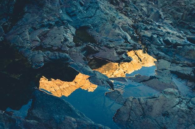 Bela foto de uma poça com o reflexo de falésias em um litoral rochoso