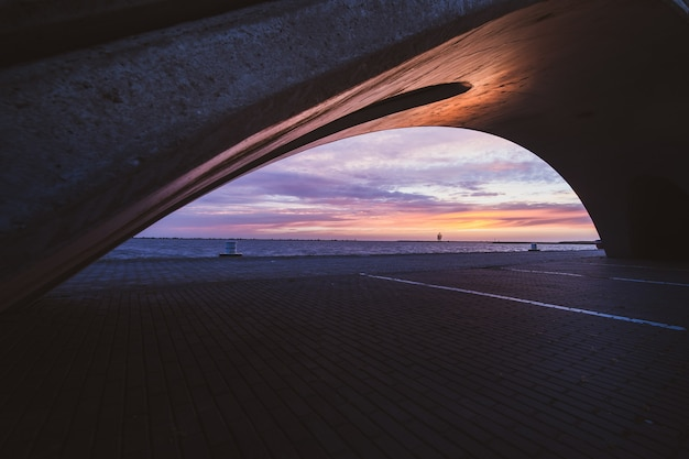 Bela foto de uma ponte em um lago reflexivo durante o pôr do sol