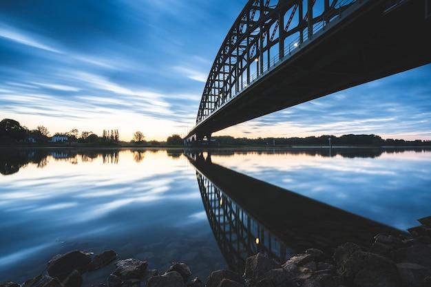 Bela foto de uma ponte sobre um lago reflexivo durante o pôr do sol