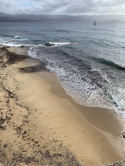 Bela foto de uma praia arenosa sob um céu nublado em ajaccio, córsega, frança