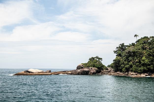 Bela foto de uma praia com colinas arborizadas na ilha grande, brasil