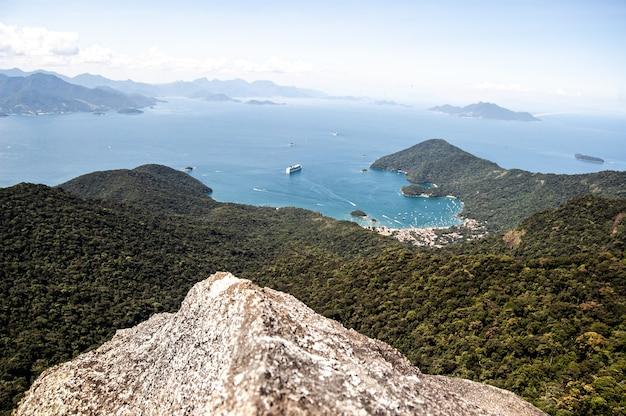 Bela foto de uma praia com montanhas arborizadas no pico de papagayo, ilha grande, brasil