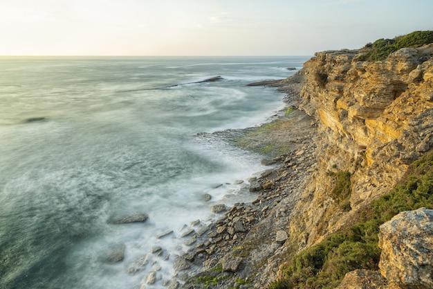 Bela foto de uma praia com um cenário do pôr do sol em um céu claro
