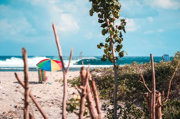 Bela foto de uma praia com um guarda-sol colorido e uma cadeira de praia com ondas incríveis